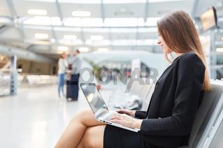 Junge Geschäftsfrau mit Laptop Computer im Flughafen