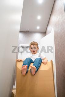 Cute little baby boy sitting on cardboard box