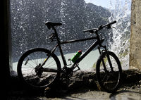 Mountain bike under a waterfall, Val de Bagnes, Valais, Switzerland