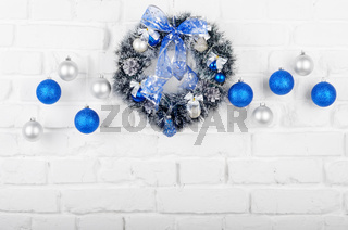 Christmas blue and silver balls and wreath on white brick wall holiday background