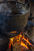 Old wood burning stove with big pan and smoke