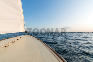 Deck of a sailboat on the ocean at sunset