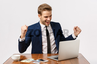 Wow thats a huge win. Attractive young blond man, businessman sitting office, looking at laptop display and smiling, clench fists relish some good news, winning, achieve goal, white background