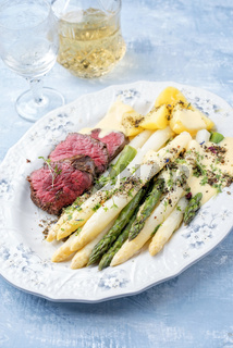 Traditional white and green asparagus with barbecue dry aged sliced beef fillet and fried potatoes served as closeup on a shabby chic design plate