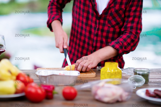 Man cutting vegetables for salad or barbecue grill