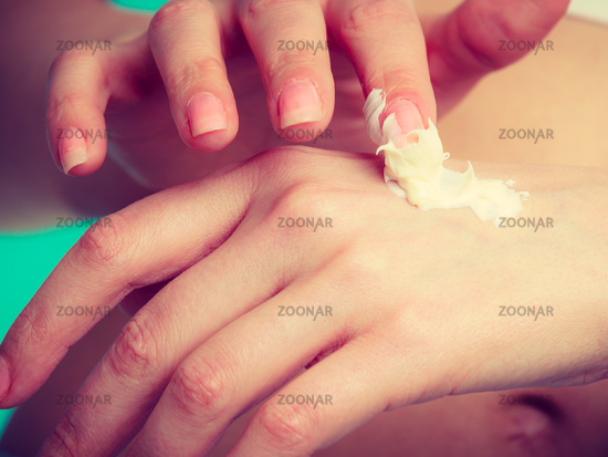 Woman putting white cream on hand