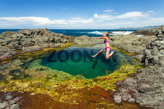 Woman jumping mid air into a beautiful clean rock pool on the coastal foreshore