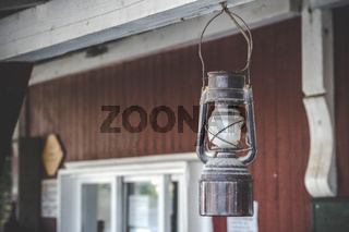 Old oil lamp hanging on a porch outside