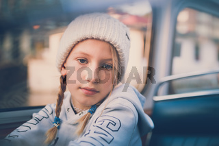Young girl on a boat trip in Amsterdam wearing bobble hat and looking straight into camera