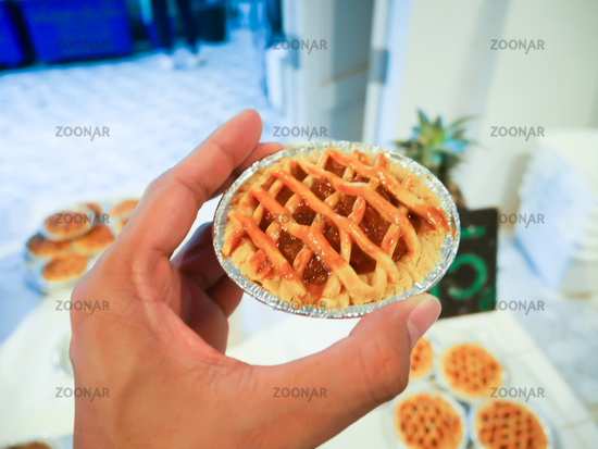Hand holding Pineapple Pie, Bakery work Pineapple pie or apple pie freshly baked from the oven