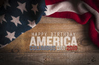 Stars and stripes scarf on a wooden table and an inscription for the Columbus Day celebrations. Columbus day 2019.