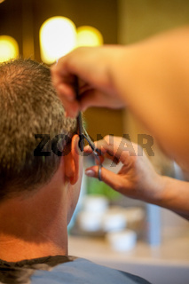 Hairdresser Shaving Man's Head With Hair Trimmer or hair clipper, seen from behind the customer.