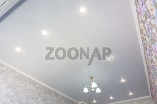 An outline of a stretch ceiling in a room with a chandelier and spotlights