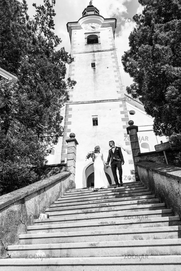 The Kiss. Bride and groom kisses tenderly on a staircase in front of a small local church.
