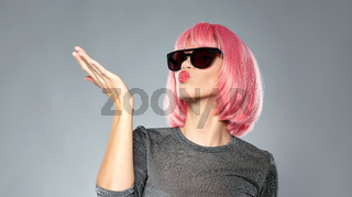 woman in pink wig and sunglasses sending air kiss