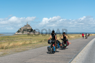 long-distance bicycle tourists visiting and traveling to the famous Mont Saint-Michel in northern France