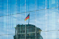 reflection of the german flag on Reichstag building in modern glass facade  -