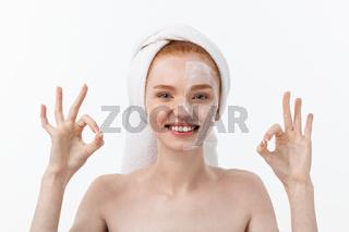 Beauty treatment. Woman applying moisturizing cream skin care product on face, making ok sign studio shot