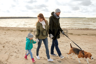 happy family walking with beagle dog in autumn