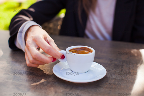 Closeup of female hands holding coffee cup