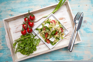 Pasta with mozarella cheese, arugula and vegetables on a wood background