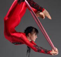 Pretty slim gymnast with red hoop studio shot