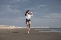 Attractive Girl Jumping on the Beach Having Fun
