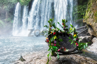 swing with flowers to beautiful waterfall