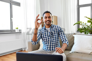 indian male blogger showing ok hand sign at home