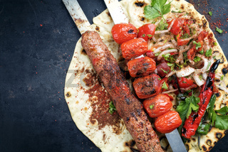Traditional Adana Kebap skewer with tomato and salad on a flatbread with copy space left