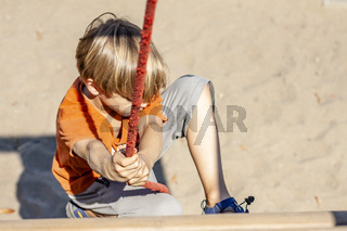 Young boy hanging on a swing at outdoor playground