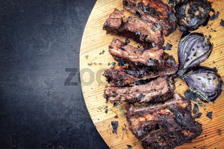Barbecue caveman spare ribs St Louis cut with hot honey chili marinade and burnt onion as top view on a board