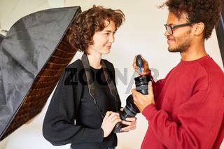 Fotograf und Fotoassistentin reinigen Kamera Objektiv