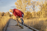 senior male runner stretching on a trail