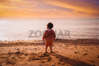 Small Child Boy Standing Alone on Beach at Beautiful Sunset Ocean Landscape Exploration Wonder Looking Out from Behind