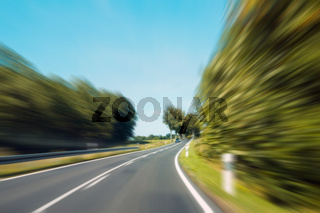driving fast concept -  motion blur on rural highway