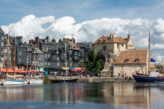 Harbor historic city Honfleur with moored sailing ships and restaurants