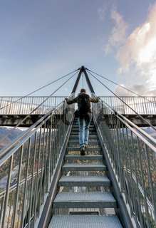 female hiker climbing up metal stairs that  lead up to an impressive lookout and viewpoint platform