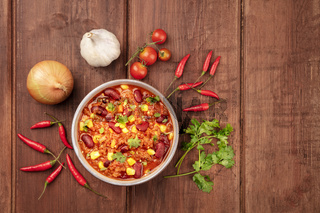 Chili con carne, shot from above on a dark rustic wooden background with ingredients and a place for text