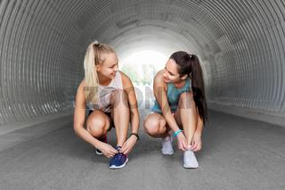sporty women or female friends tying shoe laces