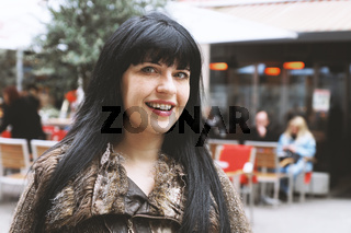 young woman in downtown pedestrian street in front of an outdoor cafe