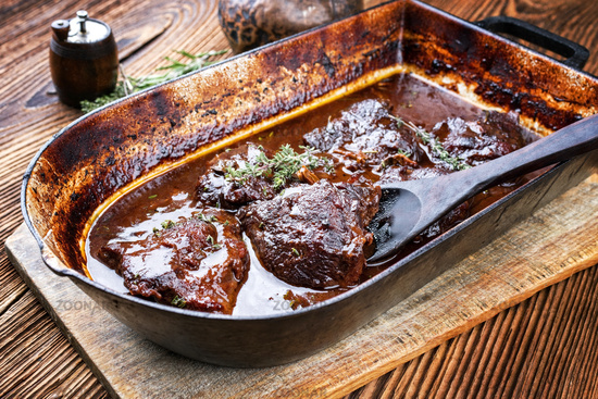 Traditional German braised veal cheeks in brown sauce with mushroom and onions as closeup in a stewpot