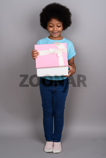 Young cute African girl against gray background