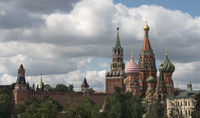 Moscow Russia View on Kremlin Towers and St. Basil Cathedral, on against cloudy sky.
