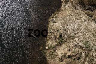 Aerial top view, countryside spring panorama of small quiet river on sunny day