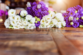 Purple and white flowers on wooden surface