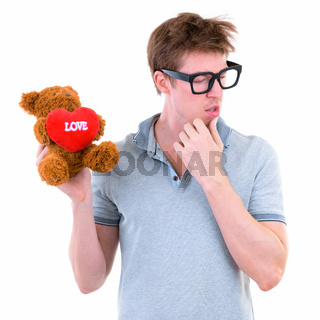Funny young nerd man with big eyeglasses holding teddy bear and thinking