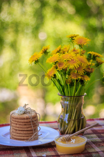 A stack of cookies, a plate of honey and flowers. Food and drink. Snack in nature