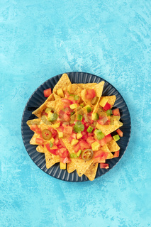Mexican nachos, tortilla chips with tomato, avocado, and cilantro leaves, shot from above on a blue background with a place for text