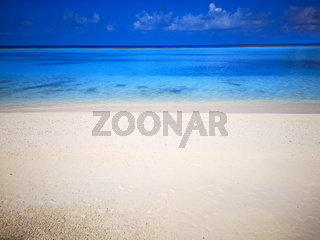 Tropical Maldives beach with white sand and blue sky.